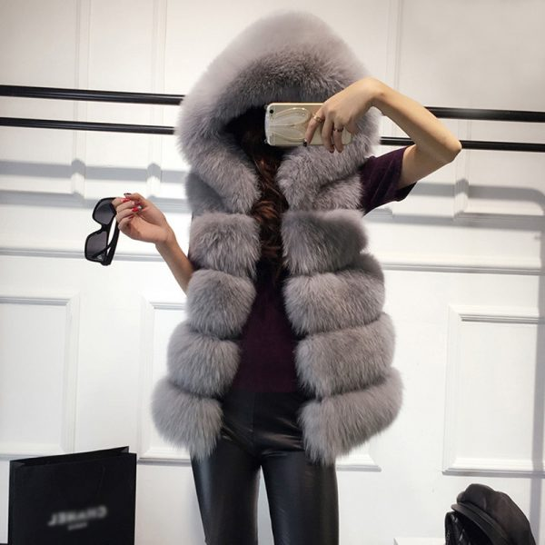 Woman wearing faux fur vest with hoodie while holding cell phone and glasses